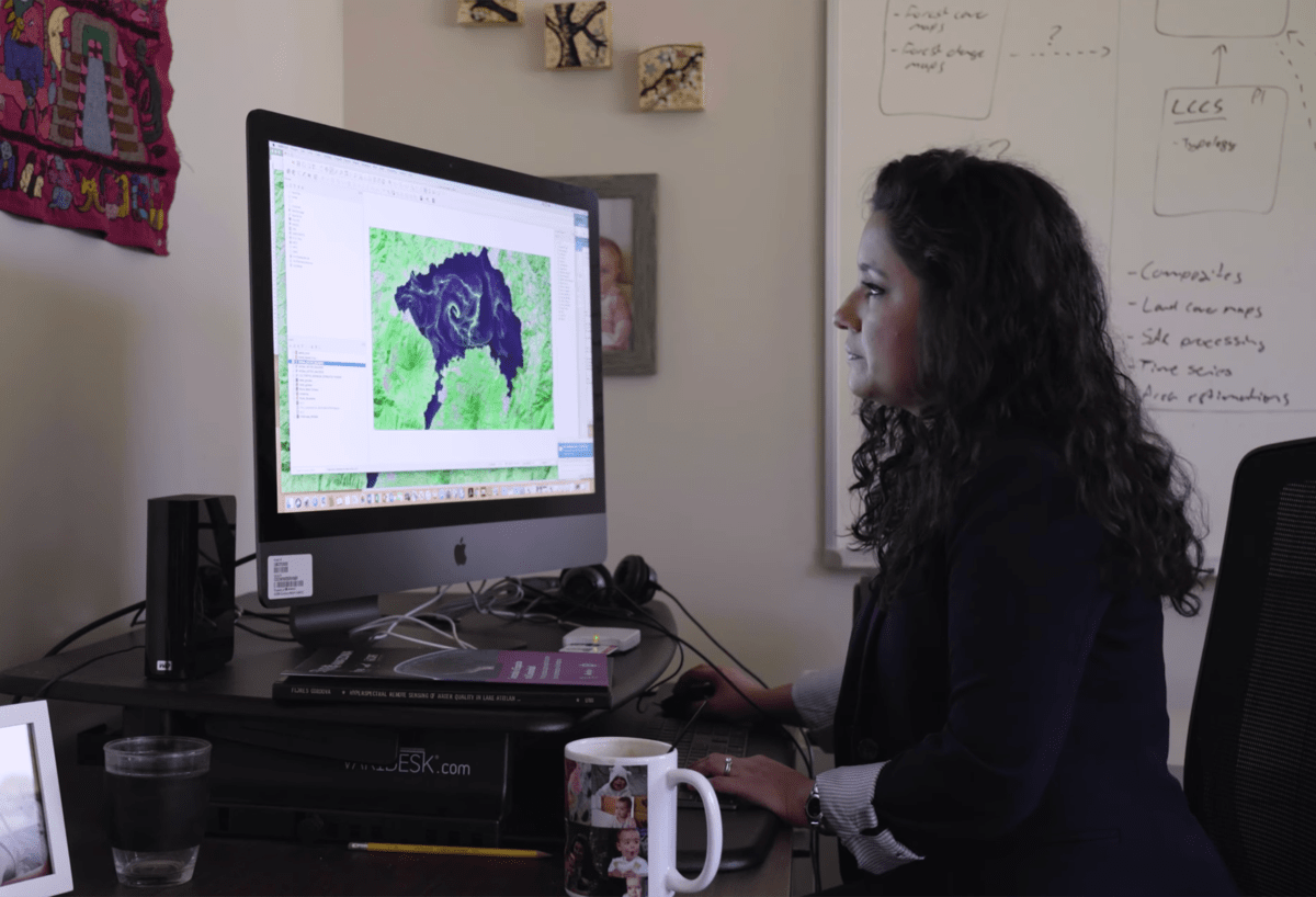 woman in a blazer in her office looking over a computer monitor with a satellite image of a lake experiencing an algal bloom