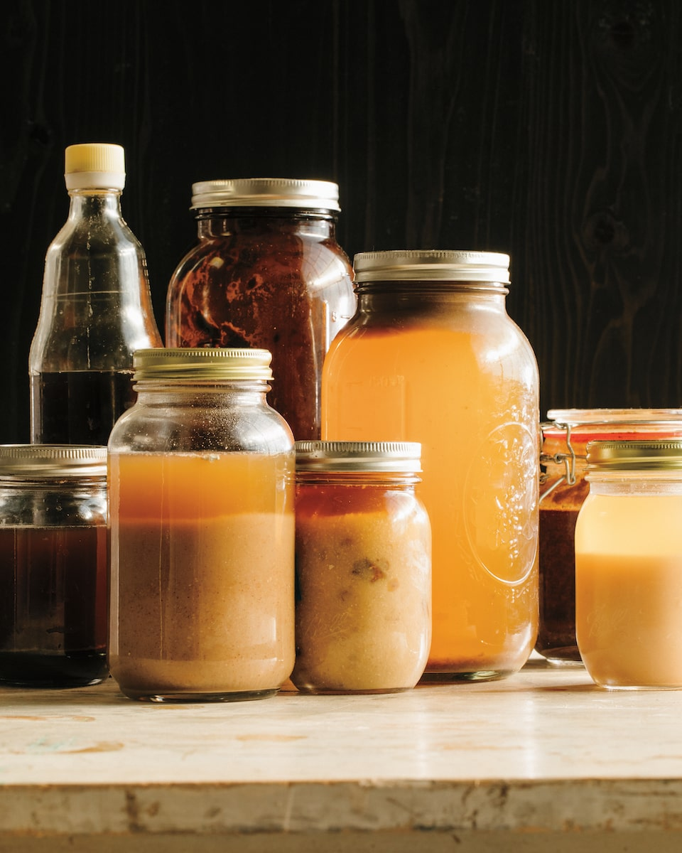 an assortment of jars with various colored liquid sauces made from koji inside