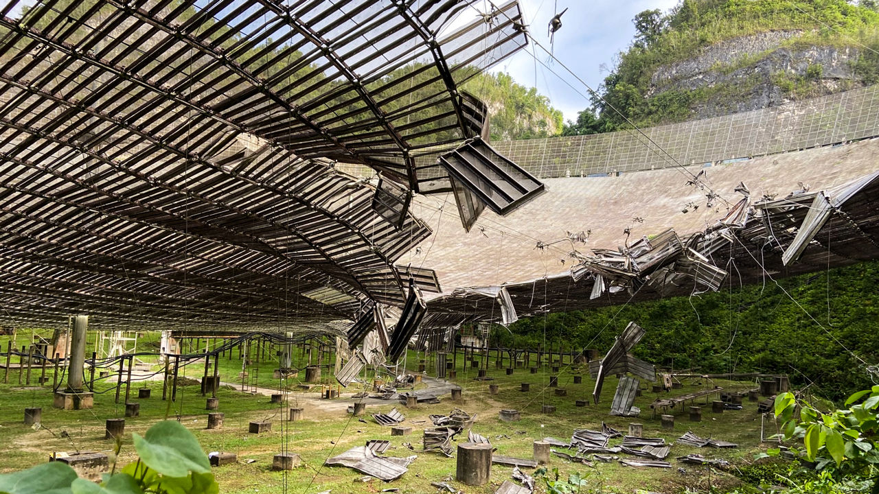 the underside of a massive dish structure, where metal panels have fallen off and some are hanging from the dish