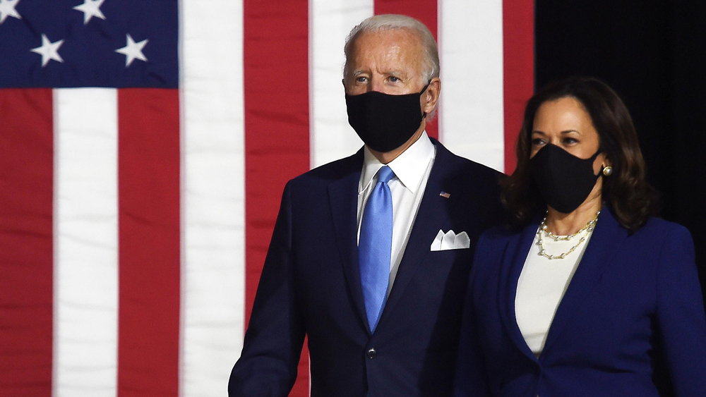 biden and harris, wearing masks, walking on stage, with an american flag in the background