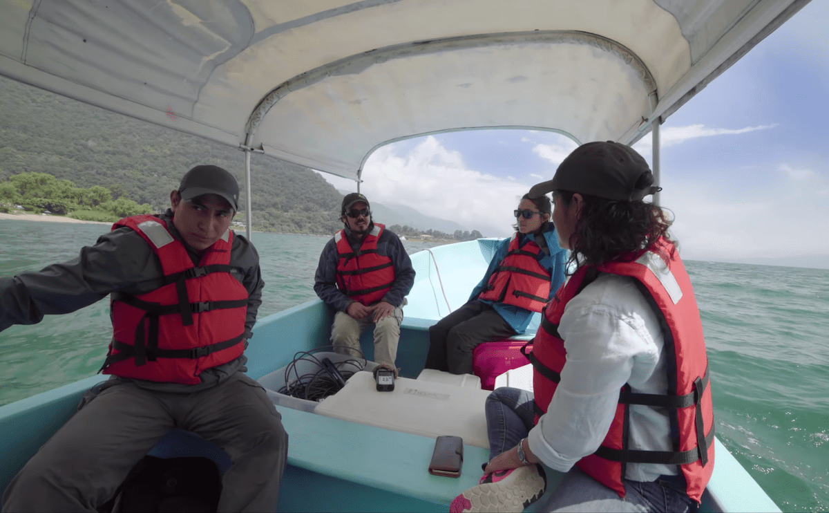 four researchers in a boat wearing life vests. they are sailing on a lake