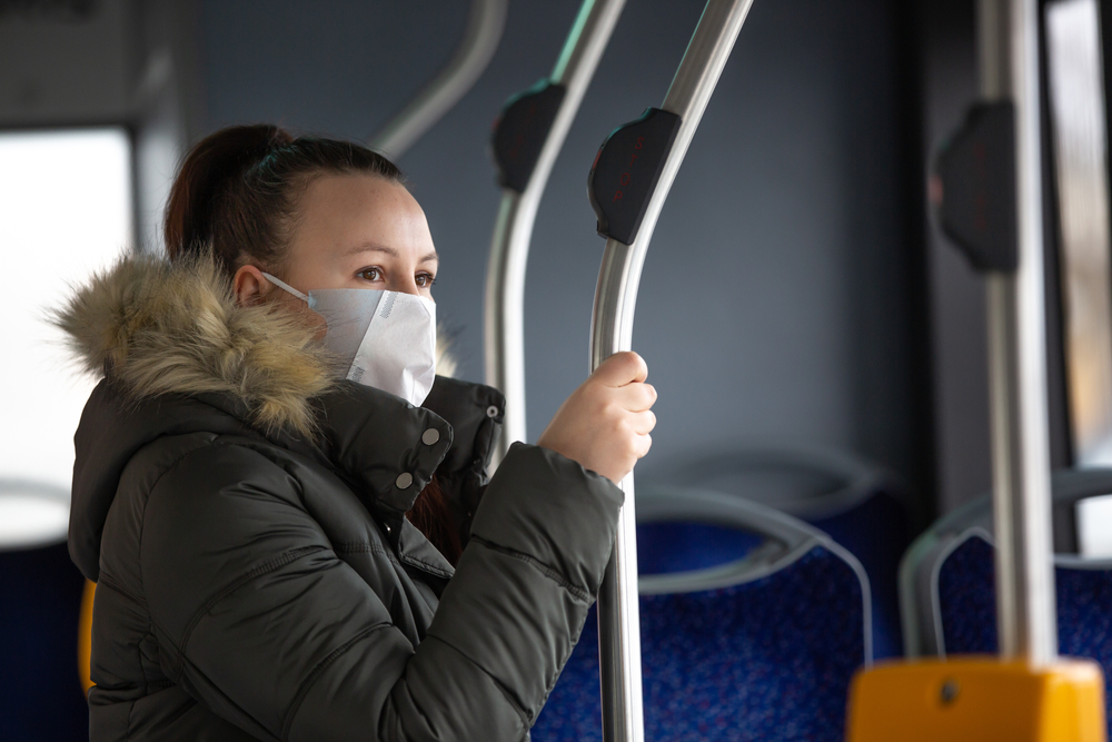 White woman wearing mask on bus holding on a pole