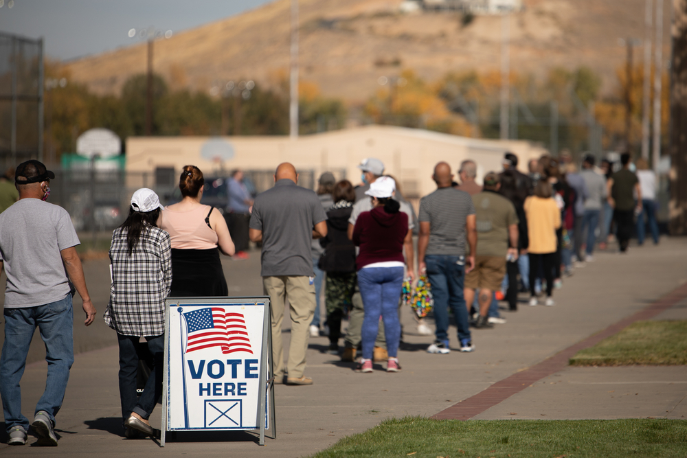 """a long line of voters outside with """"vote here"""" sign"""