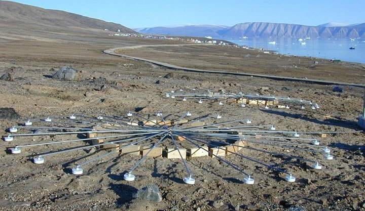 Infrasound arrays at infrasound station IS18, Qaanaaq, Greenland. Ground overlooking water with a circular arrangement of sensors all hooked together in the center used to detect infrasound.