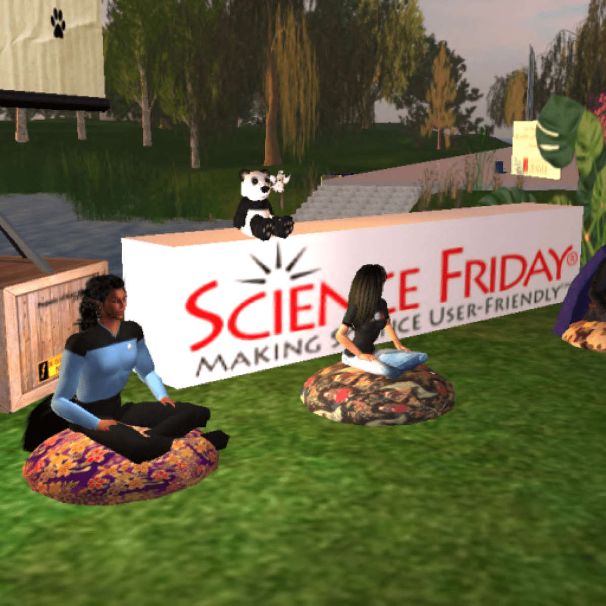 "a virtual world where a star trek uniformed avatar and a female presenting avatar with brown hair sits on cushions in a circle. behind them is a sign that reads ""science friday making science user-friendly."" a panda bear sits atop the sign"