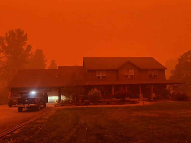 a home doused in a scary red glow cast from the smoke from wildfires in oregon