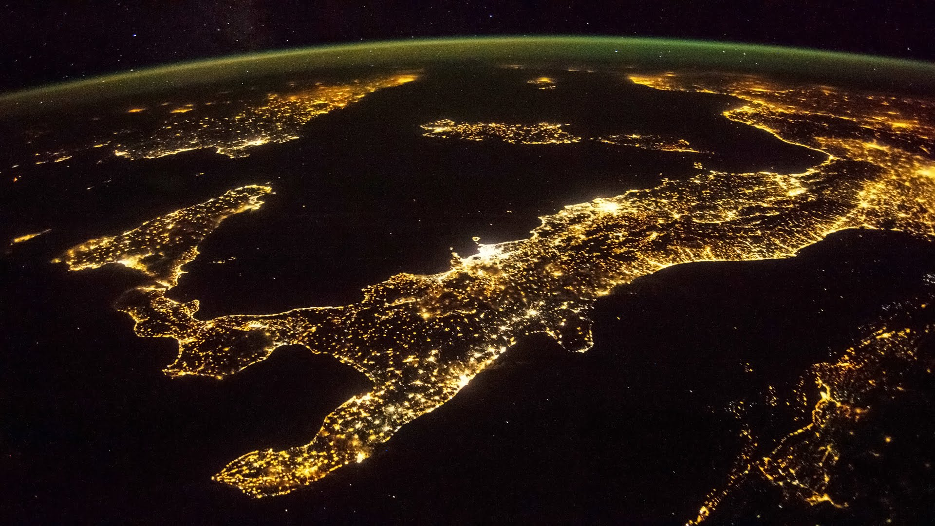 italy from space at night, with millions of lights shining