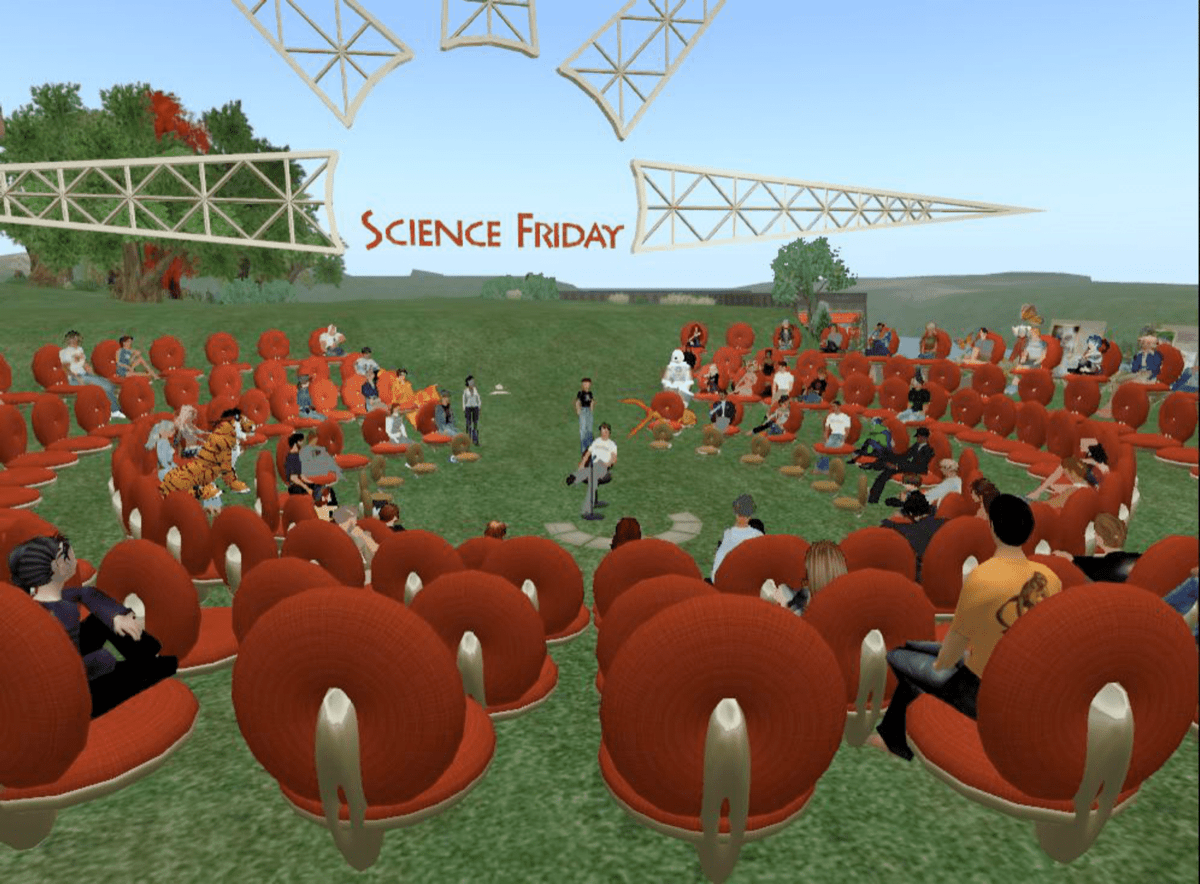 a virtual world from the late 2000s, showing an ampitheater of avatars arranged in a circle on an island. in the background is a big scaffolding structure of a sun and the science friday logo