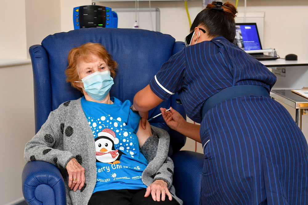 woman nurse giving older woman a vaccine shot, both wearing masks