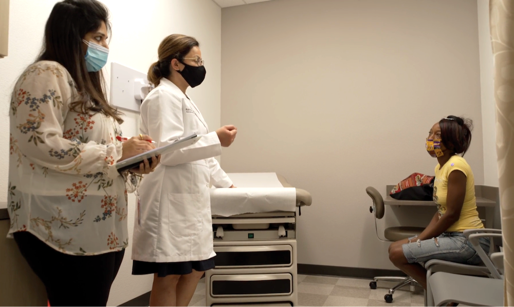 a female doctor and a female nurse wearing face masks debrief with a black woman patient in a face mask in a doctor's office