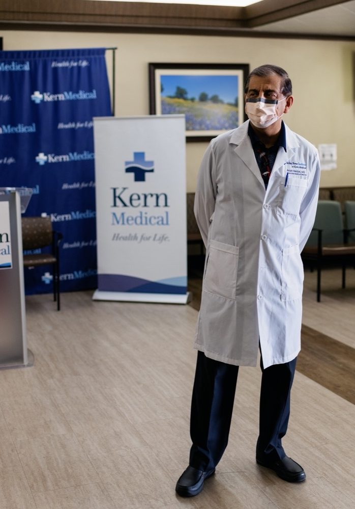 """a male doctor wearing a white lab coat and face mask stands in a conference hall. behind him is a poster that reads """"kern medical"""""""