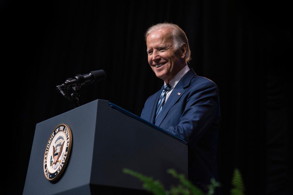biden smiling standing at a podium