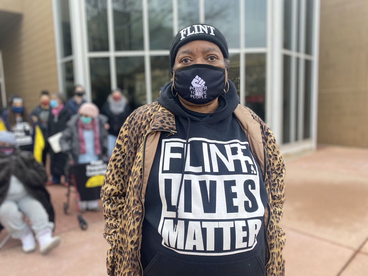 """a Black woman protester wearing a beanie that says """"flint"""", a mask that says """"power to the people"""", and a shirt that says """"flint lives matter"""""""