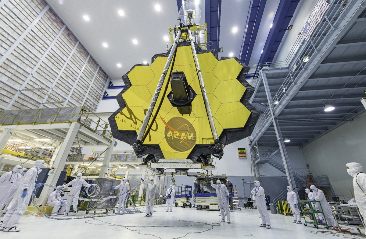 a giant gold disc made up of dozens of gold octagons in a massive hanger clean room with scientists in white protective suits around it