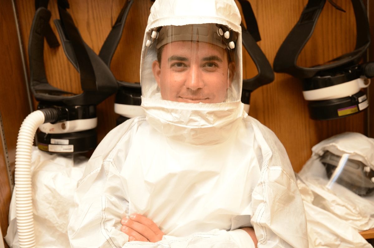 a male scientist in a hazmat suit to study coronaviruses in a biosafety lab