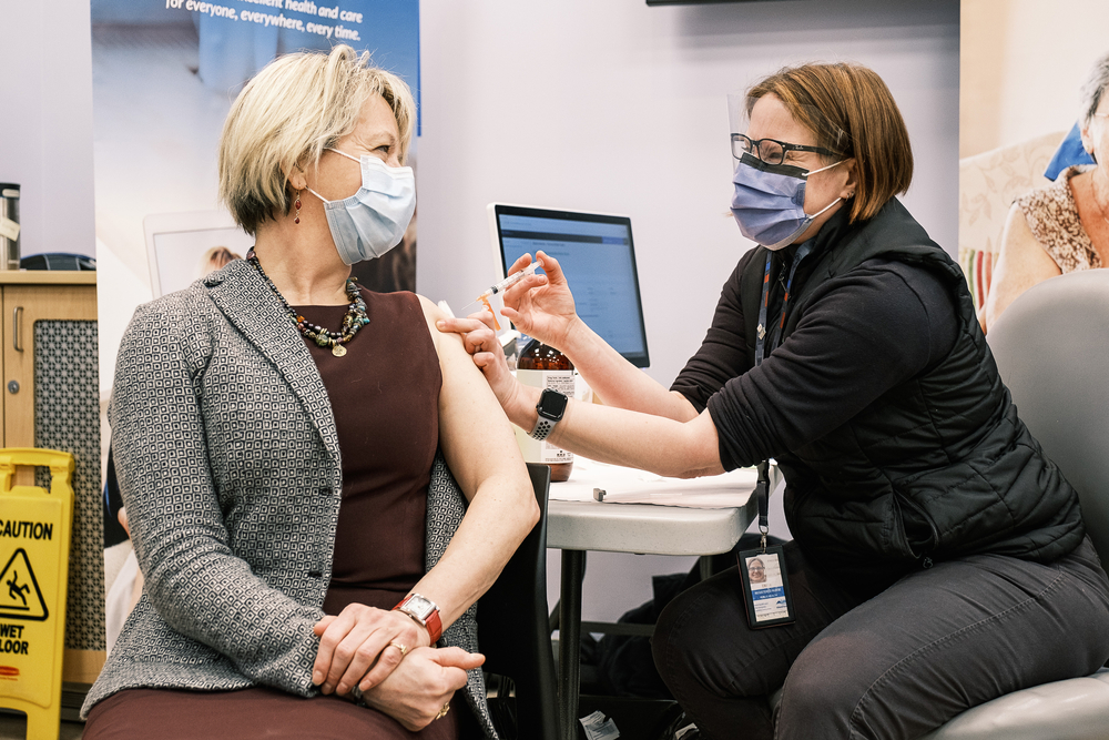 White woman giving another white woman a vaccination, both wearing masks