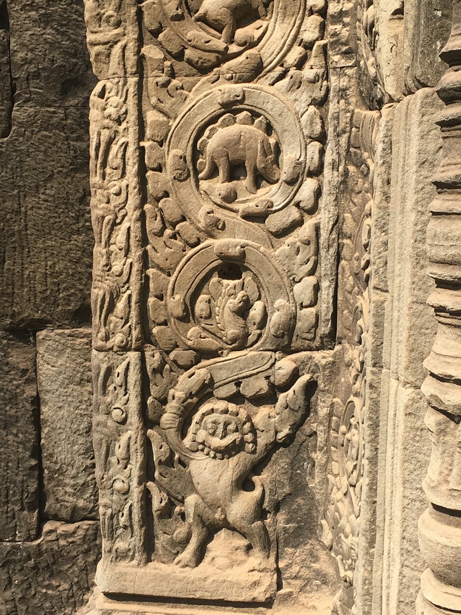 an intricately stone carved wall with various creatures and designs.