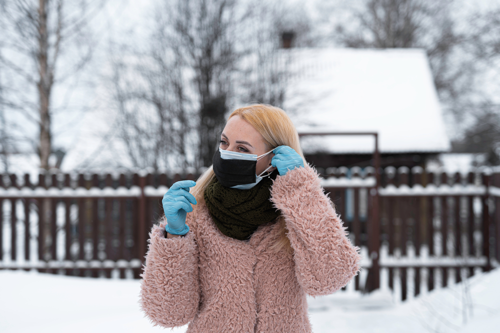 a White woman outside in a coat wearing gloves applying two masks to her face, and there's snow on the ground