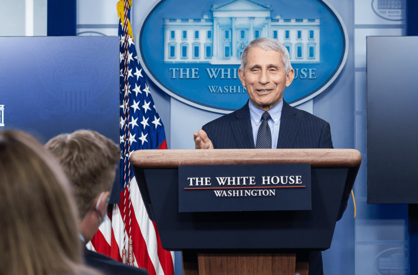 a smiling fauci speaks behind a podium in the white house briefing room