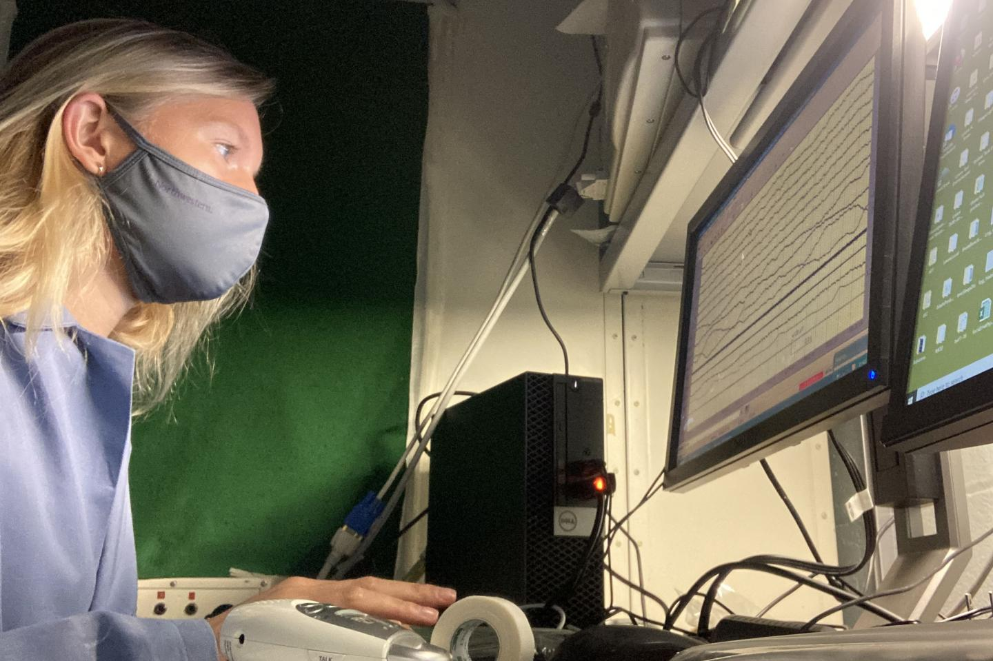 a woman in a face mask at a computer monitoring a graph of lines running horizontally across the screen