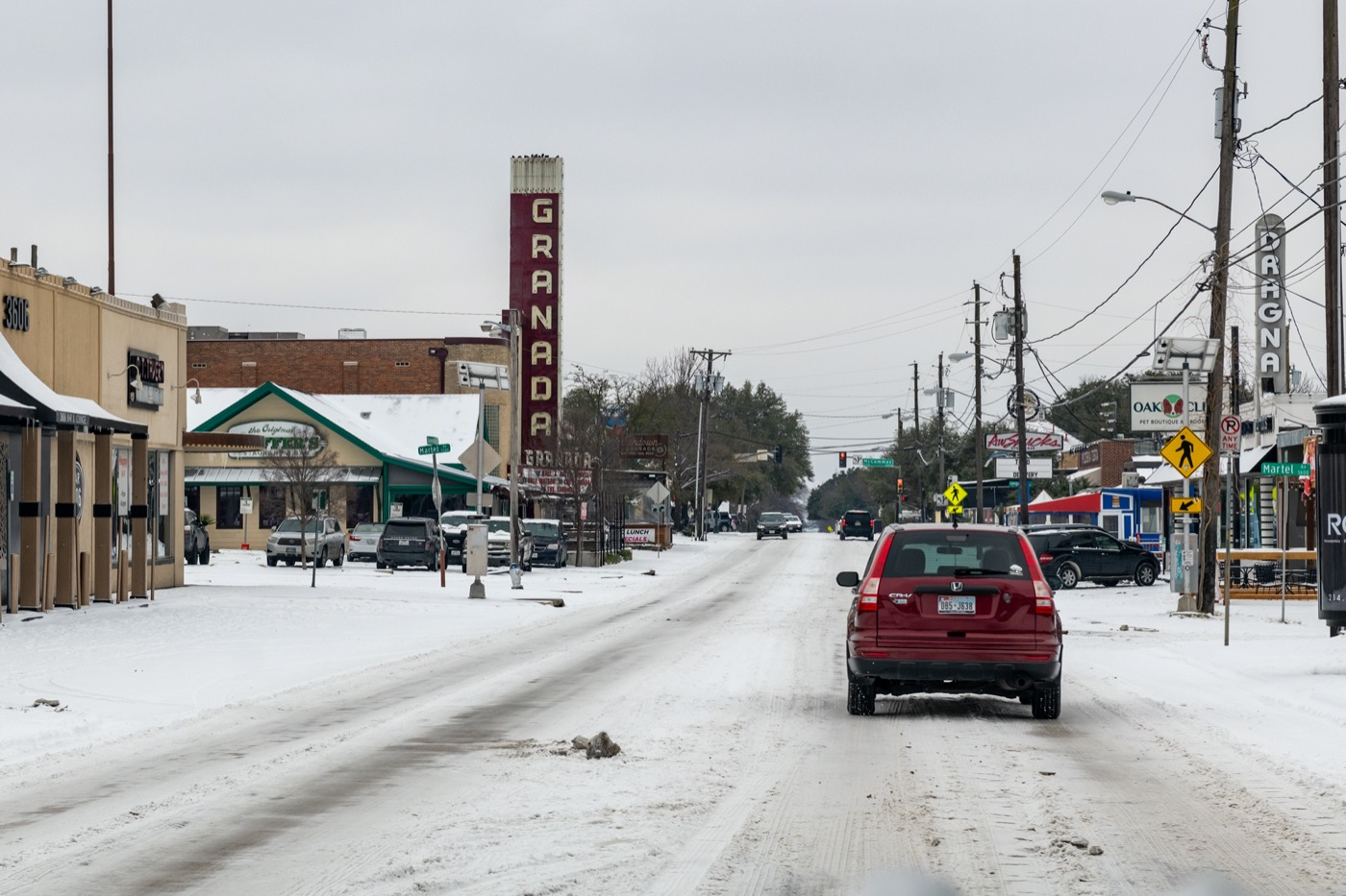 a snow covered street in dallas texas. lots of ice still on the street as a car drives down the street, lined with shops and a movie theater. no electric lights are present