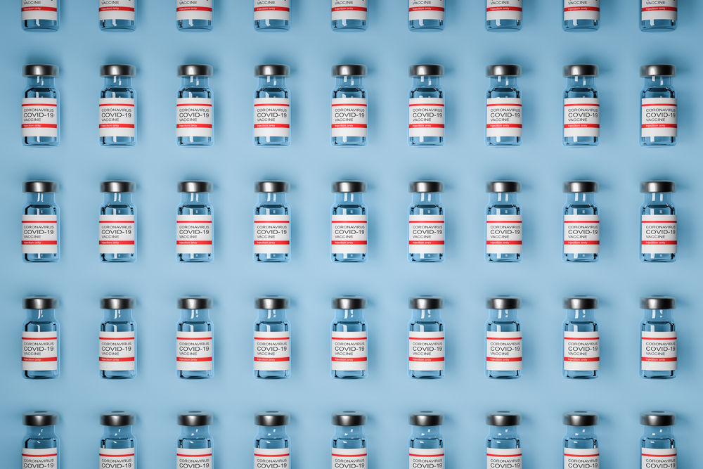 pattern of vaccine bottles against covid-19 with injection fluid. Coronavirus vaccine on Blue background