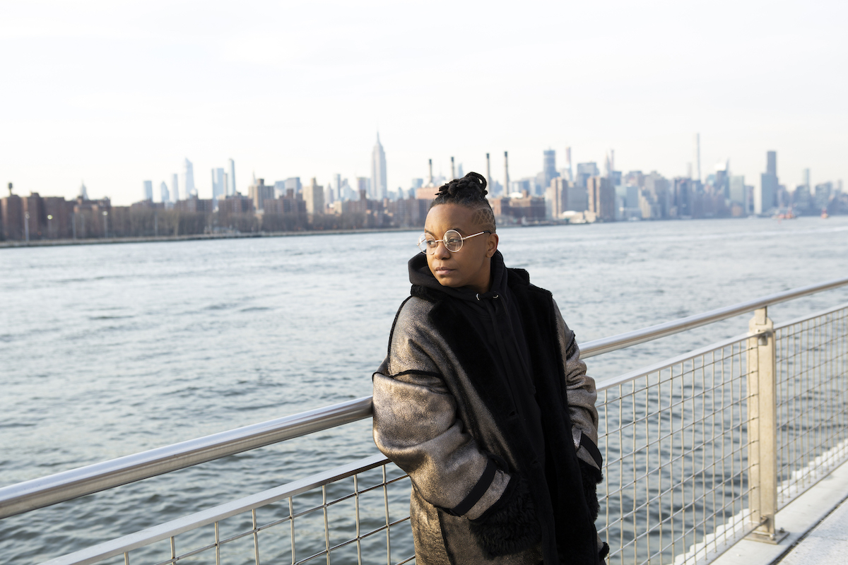 a black transmasculine person standing alone by the water's edge with the nyc skyline in the background, looking out into the distance