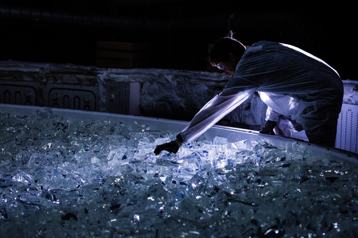 eerie-looking photo of a worker in the dark arranging large chunks of glass on a huge plate. the worker is reaching their arm out