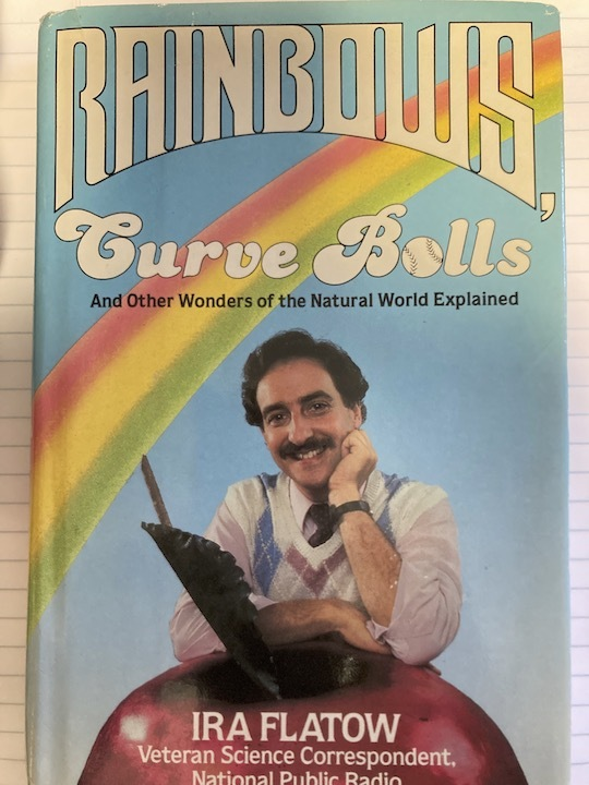 """a vintage book cover of a man with a moustache and propped up on an apple. on the cover is a rainbow above him with the title """"rainbows: curve balls and other wonders of the natural world explained"""""""