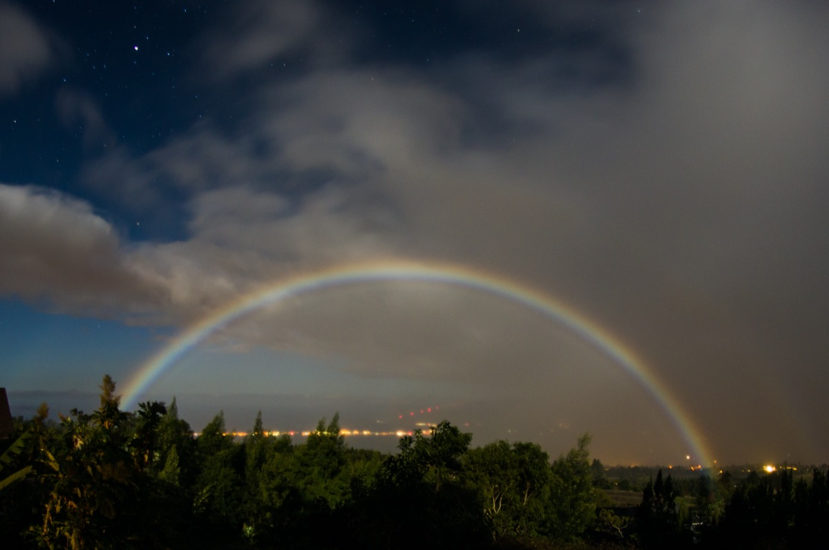 a faint rainbow seen arching over trees and city lights at night. you can see stars in the background