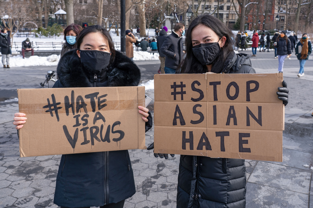 two asian women wearing masks and jackets outside in the snow carrying cardboard signs that say 'hate is a virus' and 'stop asian hate'
