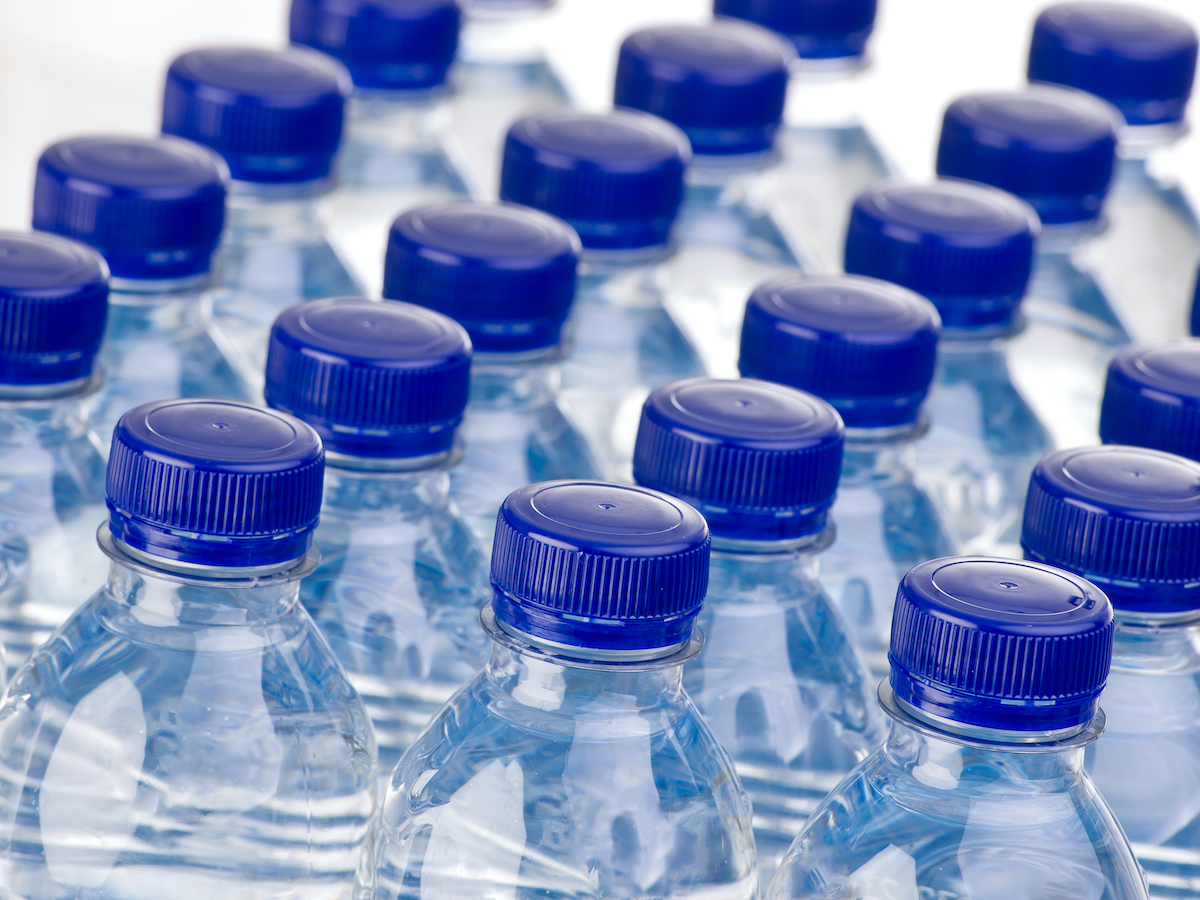 close up of rows of blue plastic water bottles with dark blue caps, all closed