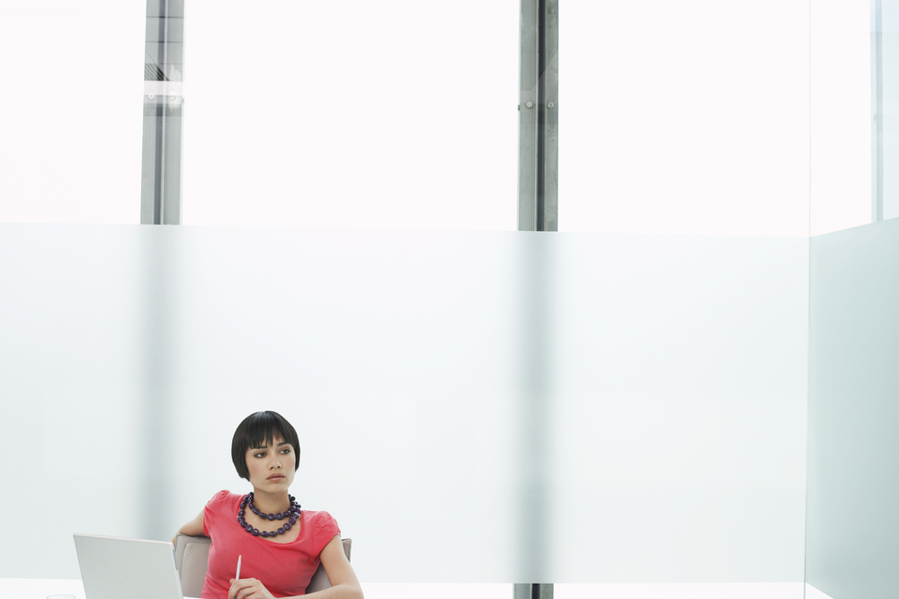 a woman thinking and staring off in the distance as she sits with a laptop in a modern cubicle office