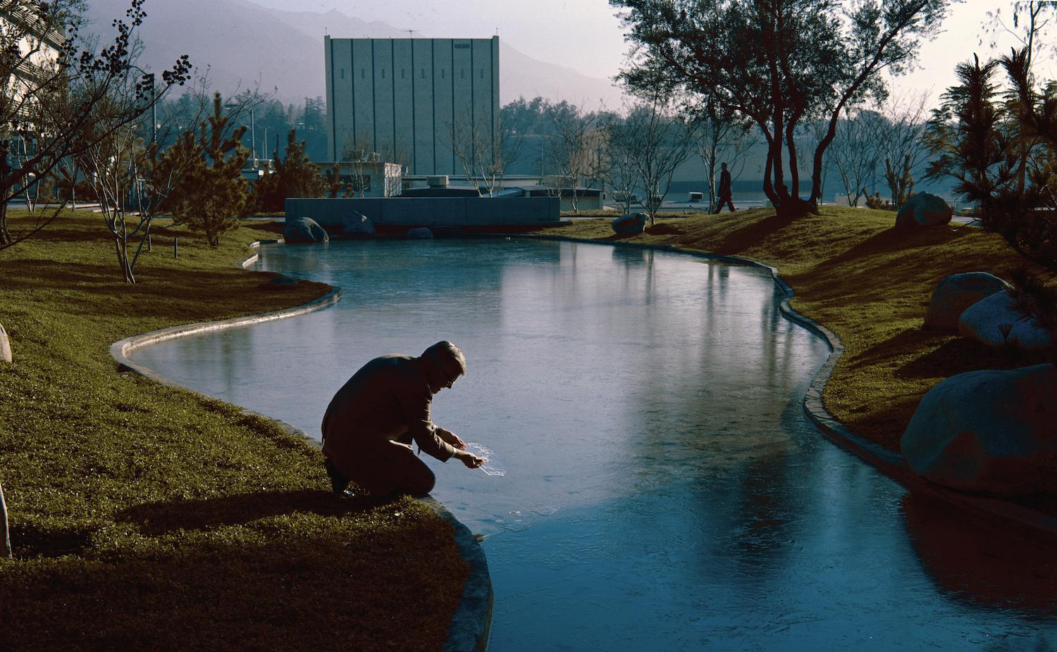 a winding human-made river cutting through grassy hills. in the background is a square white building and in the foreground, shadowed, is a person crouching down near the water