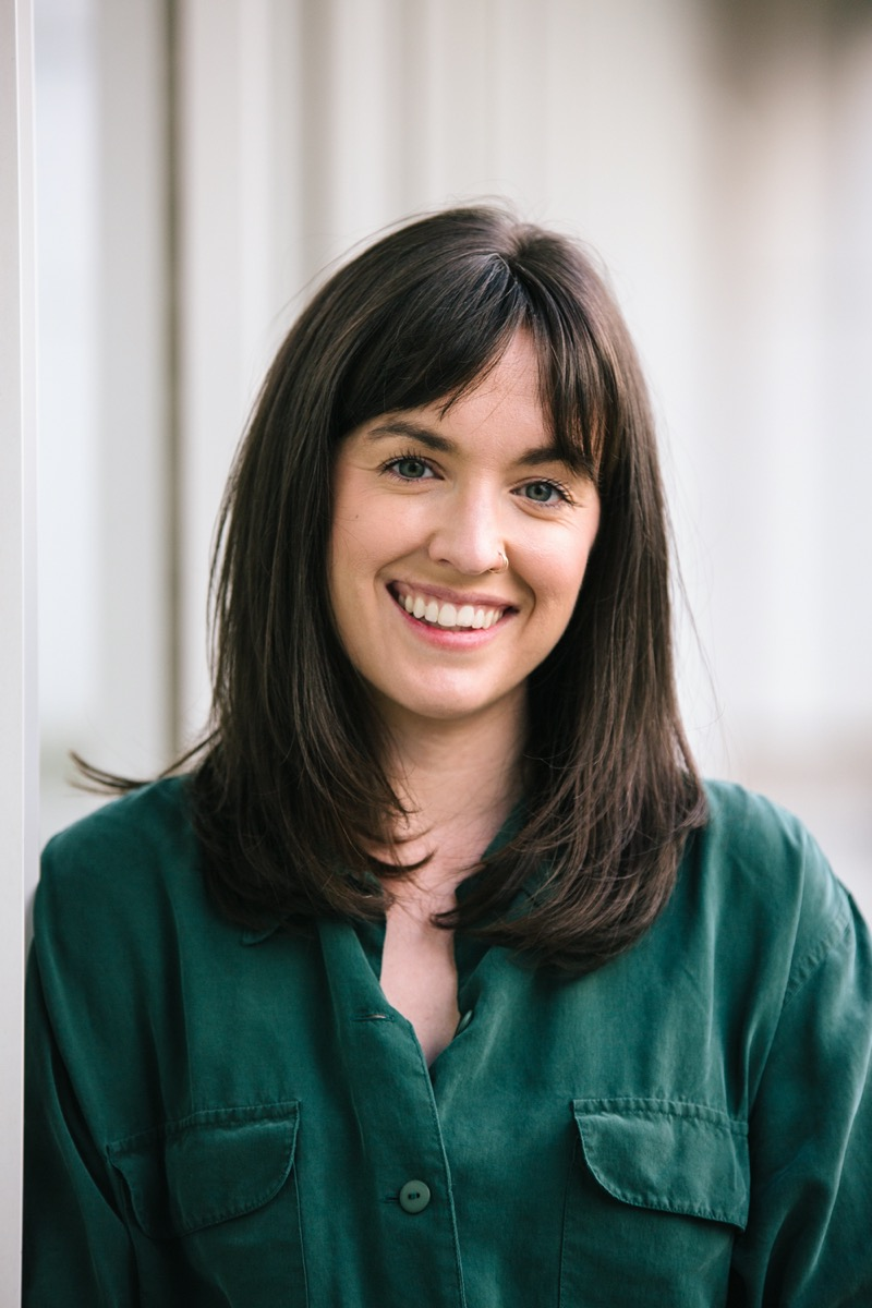 a professional headshot of a woman with brown hair wearing a green shirt