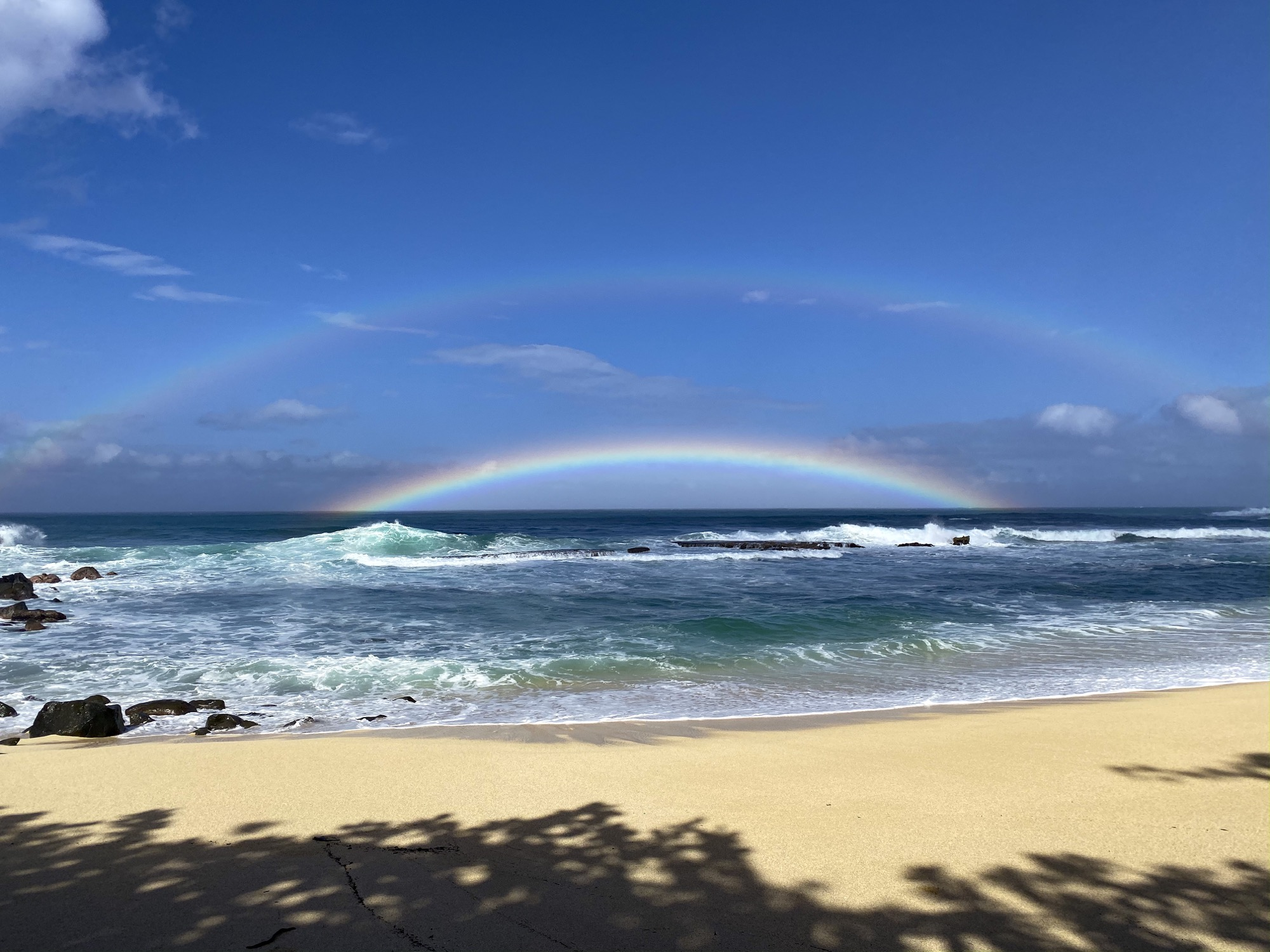 a double rainbow, the primary bow hanging low in the horizon over a beach