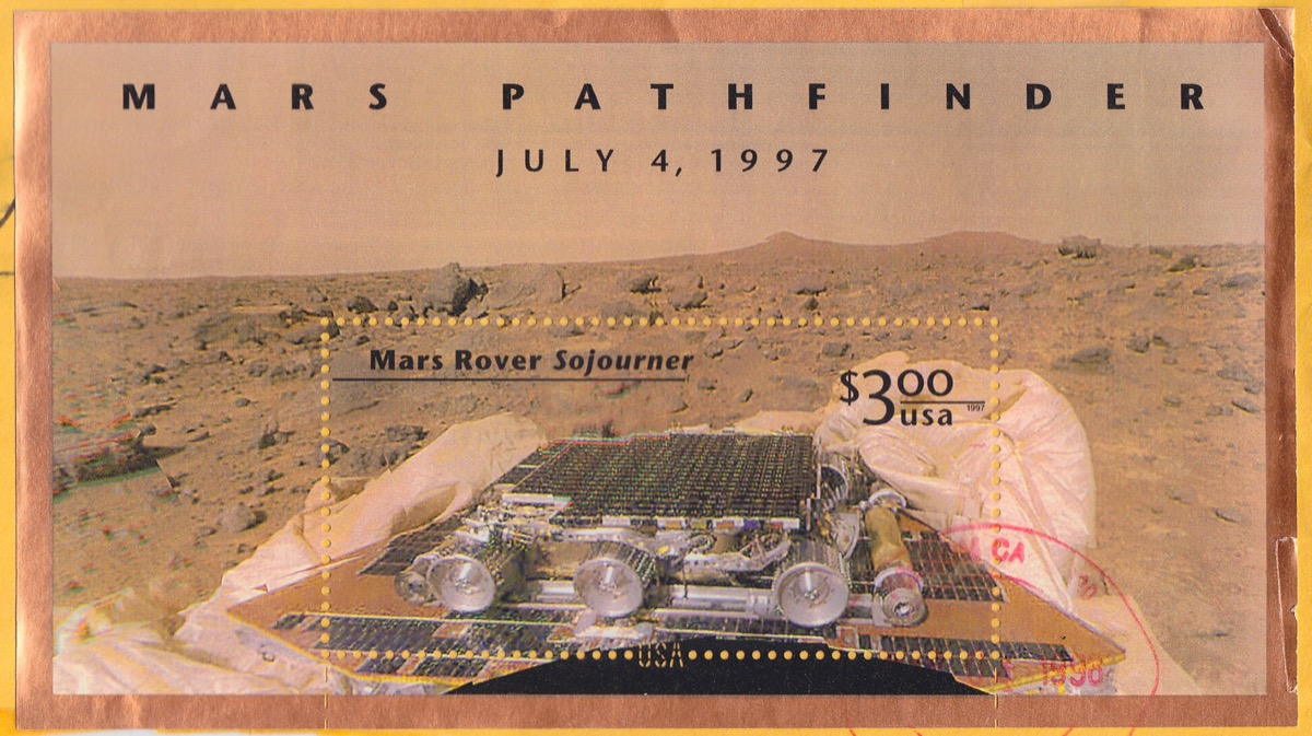 """a colorized post stamp of the desert landscape of mars with a small rover on the platform of a lander. the post stamp reads """"mars pathfinder july 4, 1997"""" and below """"mars rover sojourner $3.00 USA"""""""