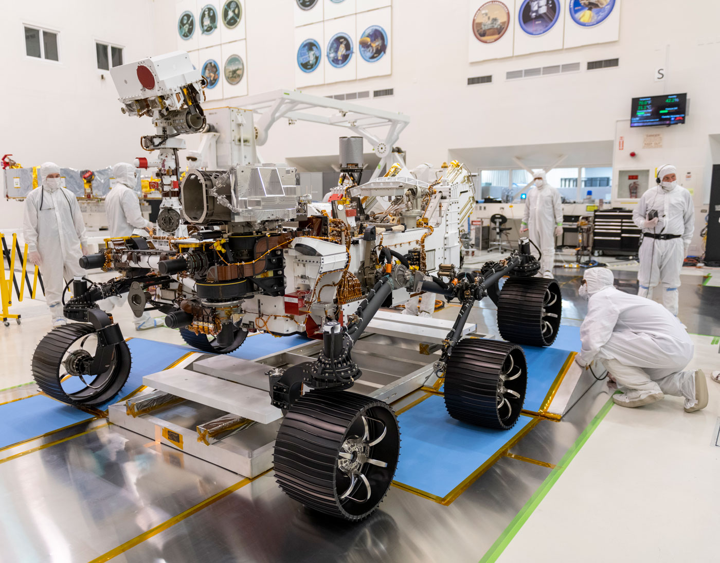 a large robotic rover with six wheels in its skeletal form being developed in a white sterile lab. the rover is about the size of a two-car door. people in white hazmat suits work on the rover