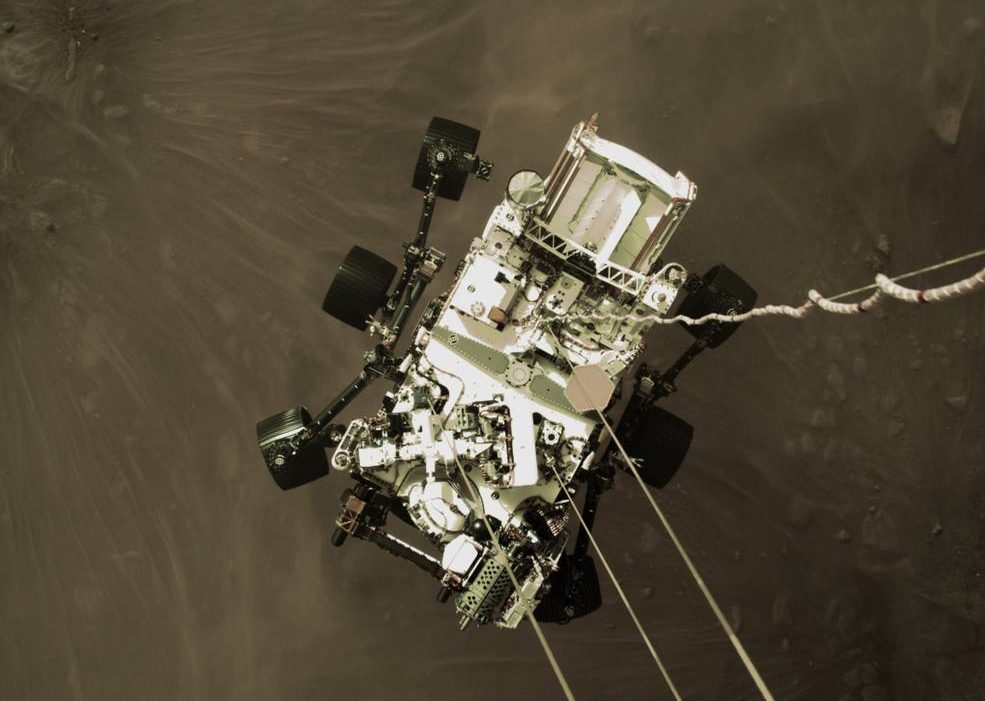 a color image aerial view of a large six-wheeled robotic rover parachuting down onto the desert environment of Mars Jezero Crater