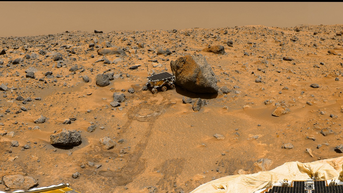 a color image of a orange dusty desert looking out at a small six-wheeled robotic rover with a solar panel on its roof. it is close to a large rock.
