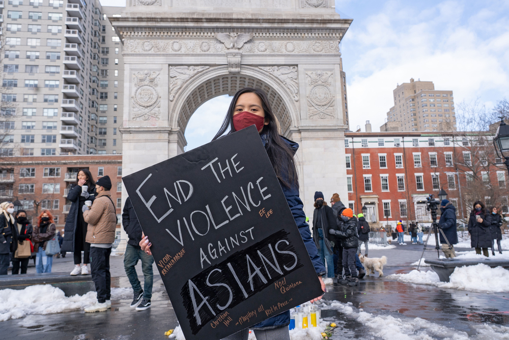 a young asian woman holds a sign that reads end the violence against asians in a snow covered plaza with an archway in the background