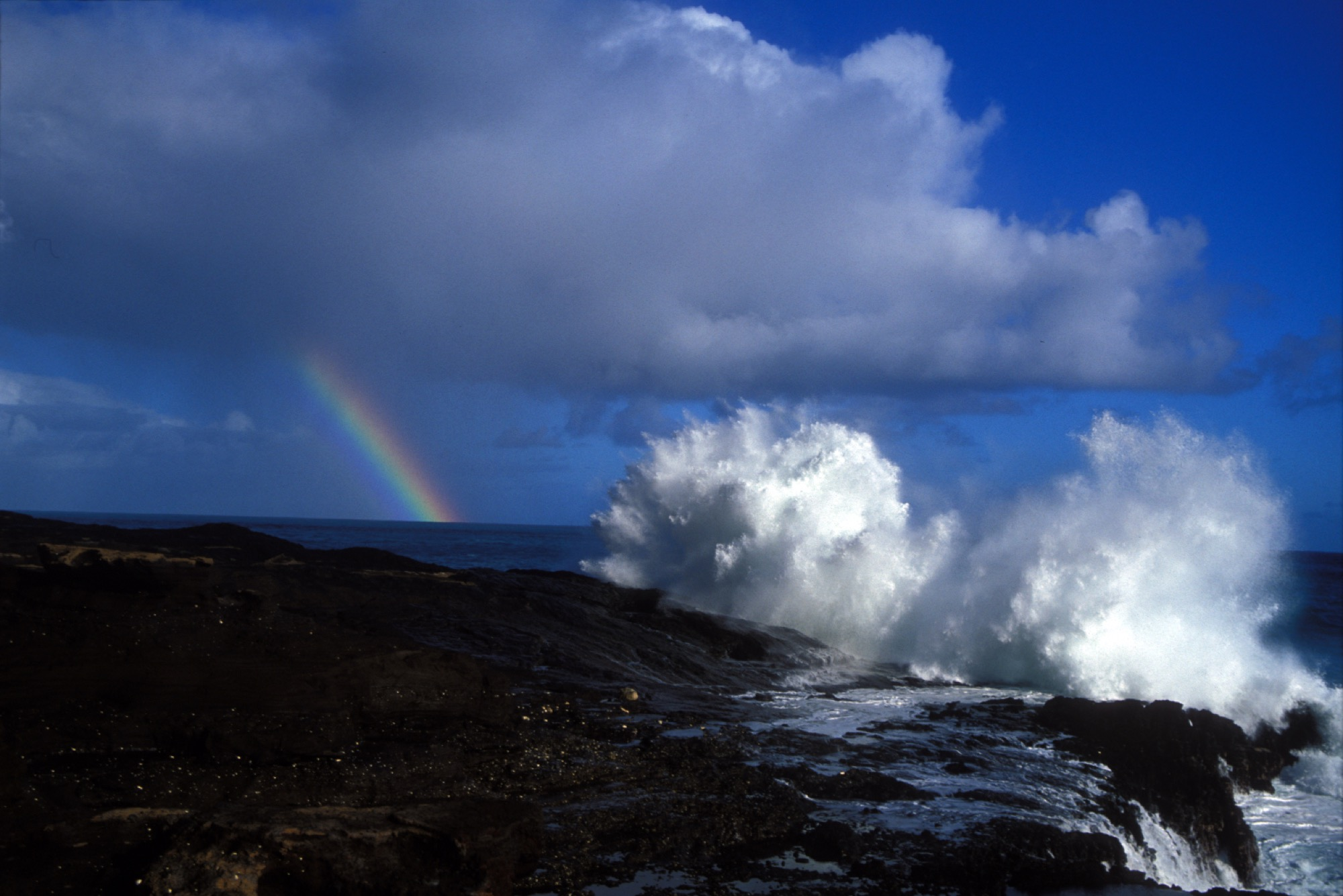 waves crash on a rocky shore. in the distance are patchy clouds and a pillar of a rainbow coming down from the cloud and disappearing into the ocean