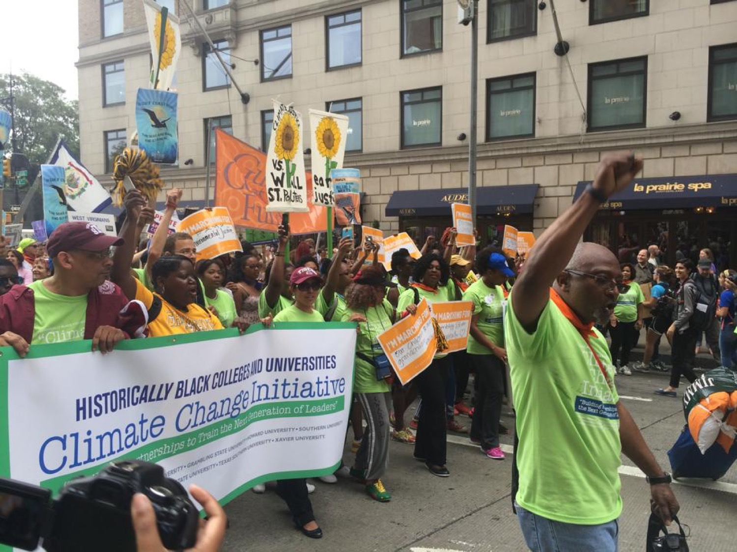 a group of black people coming together to march in a protest against climate change. their hands are raised in the air and they hold a banner that reads historically black colleges and universities climate change initiative