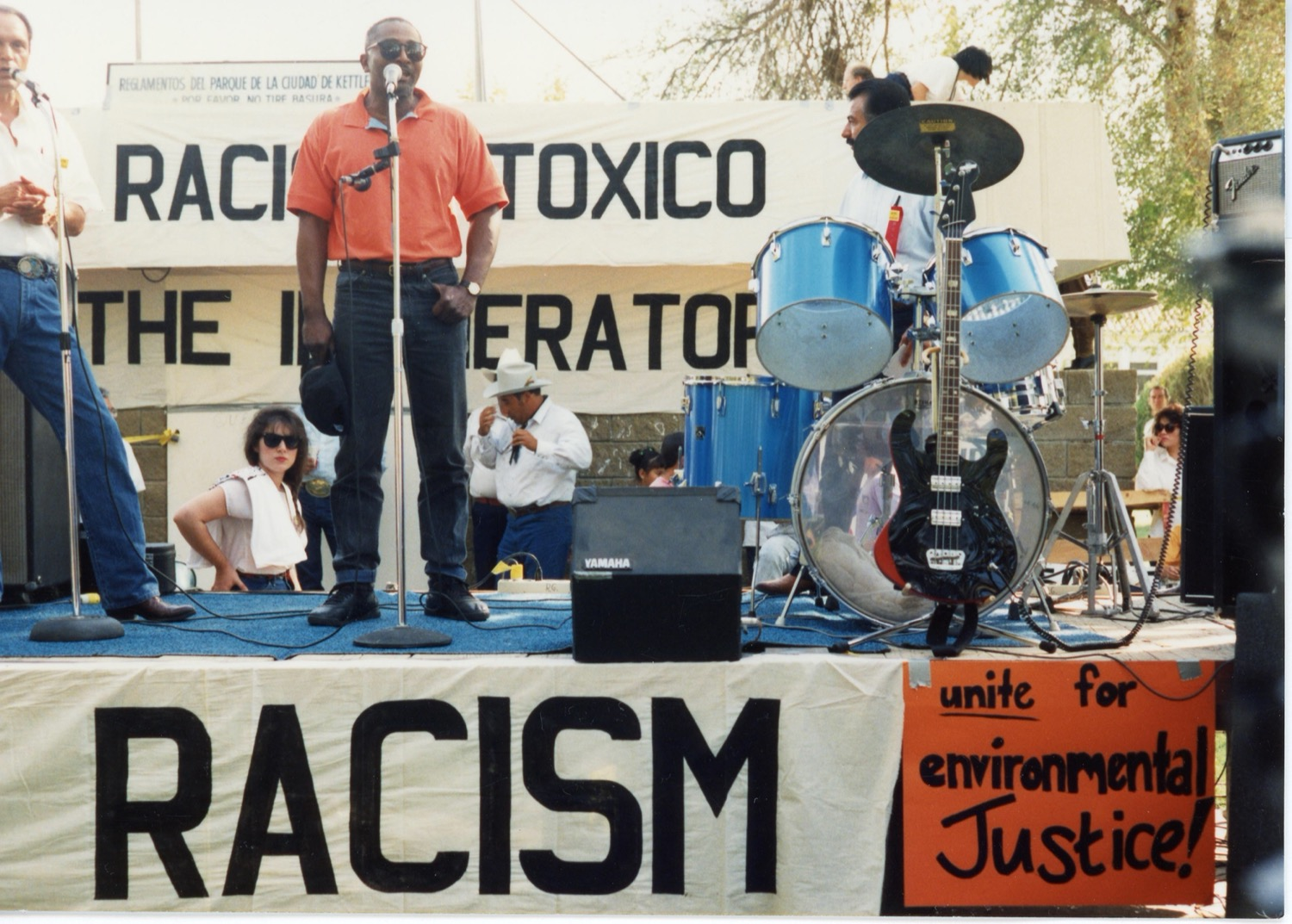 """a black man in a red polo stands up on a stage and speaks in a mic at a protest rally. next to him are a band's instruments. signs read """"toxico"""" and """"racism"""" and """"unite for environmental justice"""""""