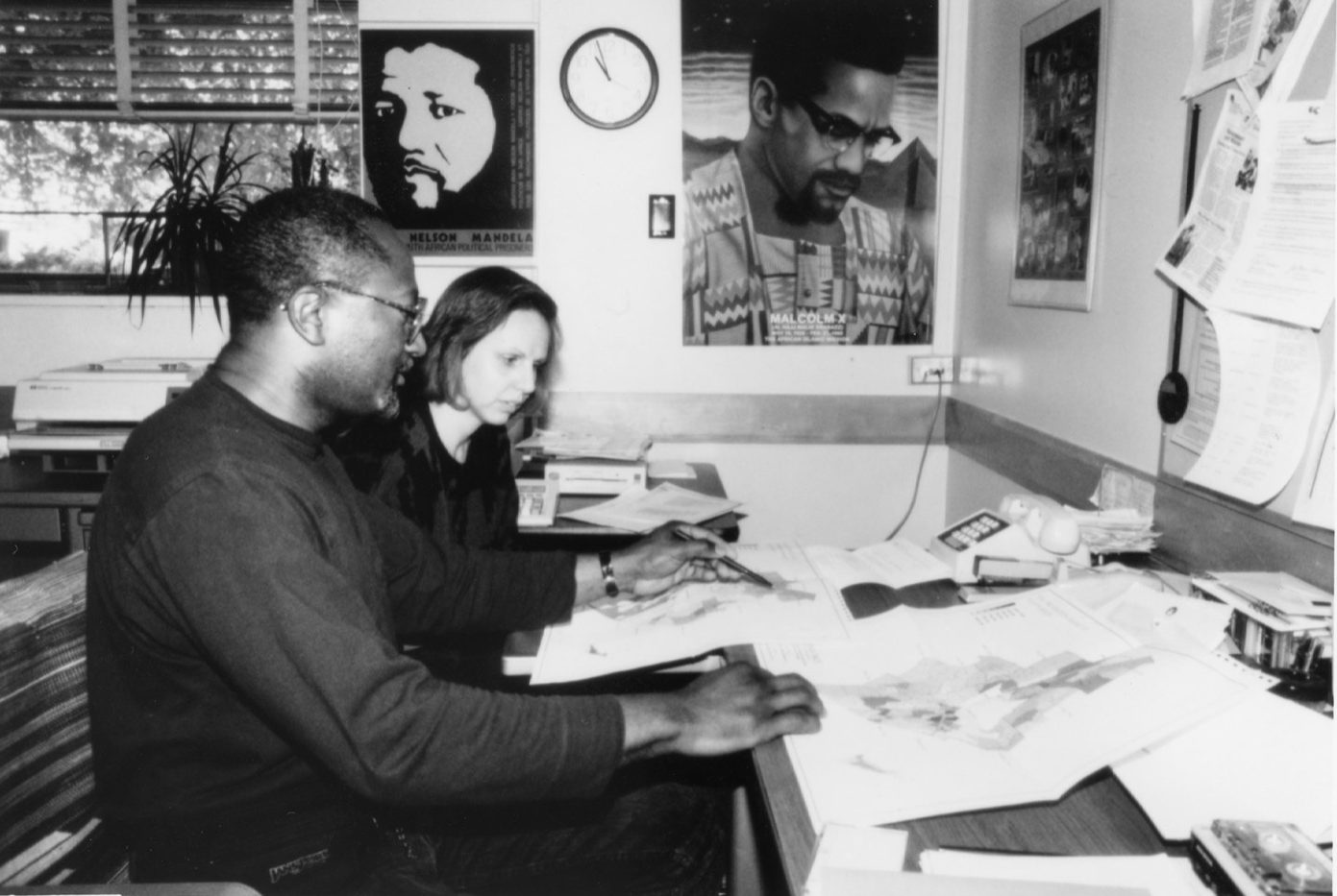 a black and white photo of a black professor teaching a graduate student. they are studying printout maps together