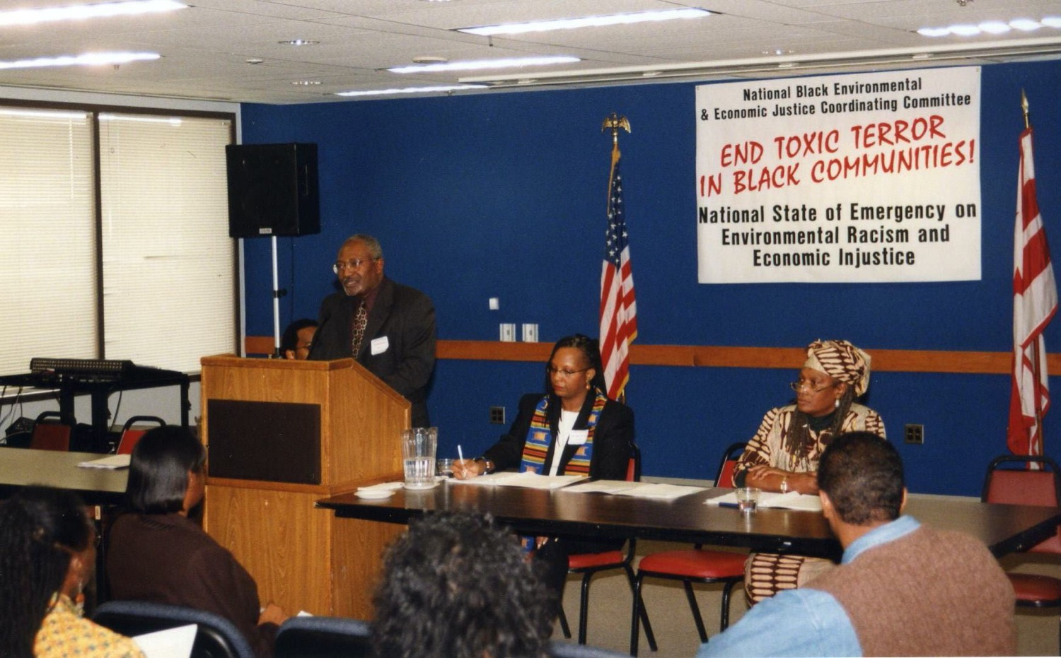 """a black man speaks at a podium. next to him are two other black leaders at a panel table. behind them is a sign that can be partially read """"end toxic... in black communities."""""""