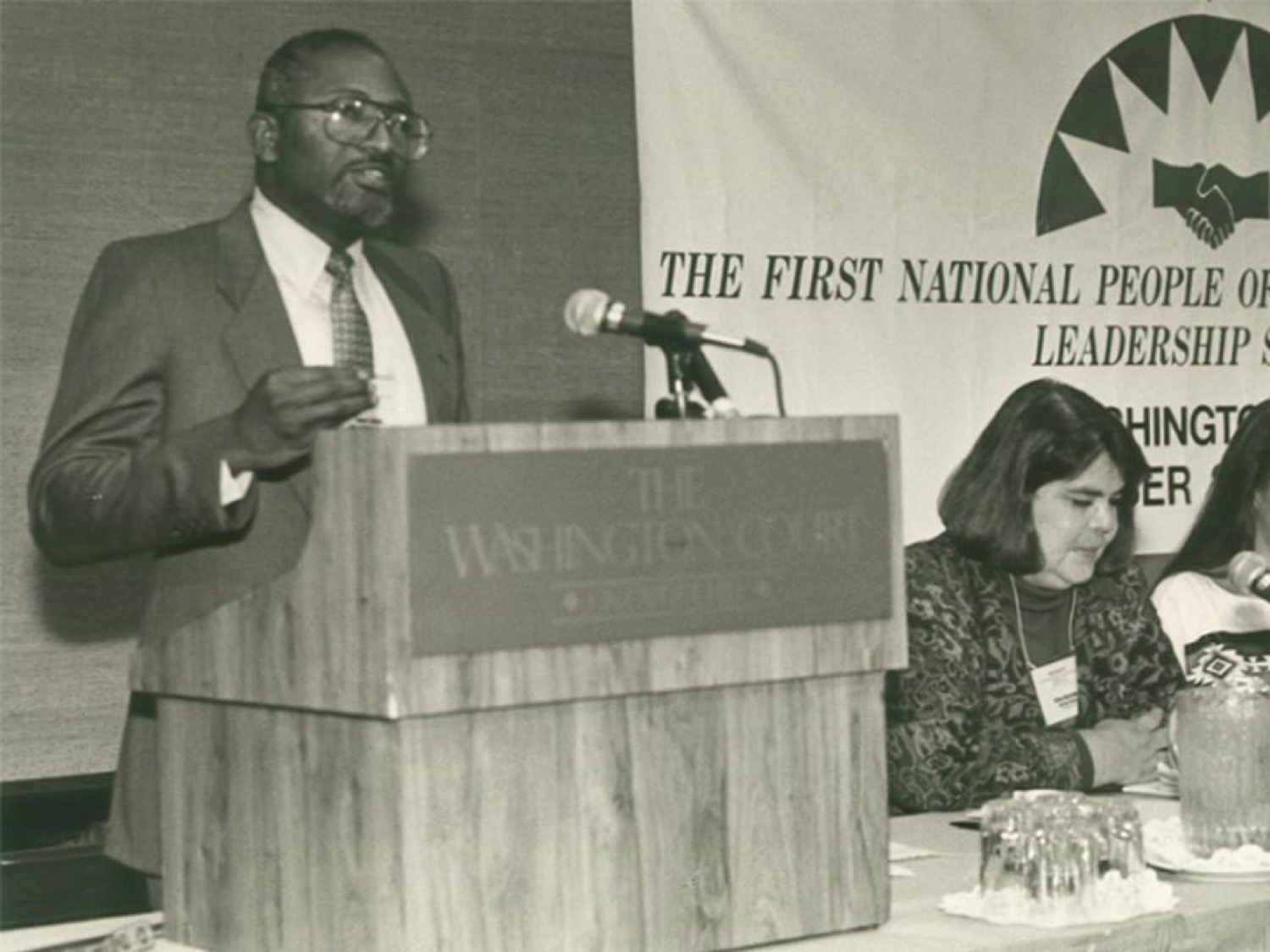 a black and white image of a black man in a suit speaking at a podium in front of a sign that said the irst National People of Color Environmental Leadership Summit