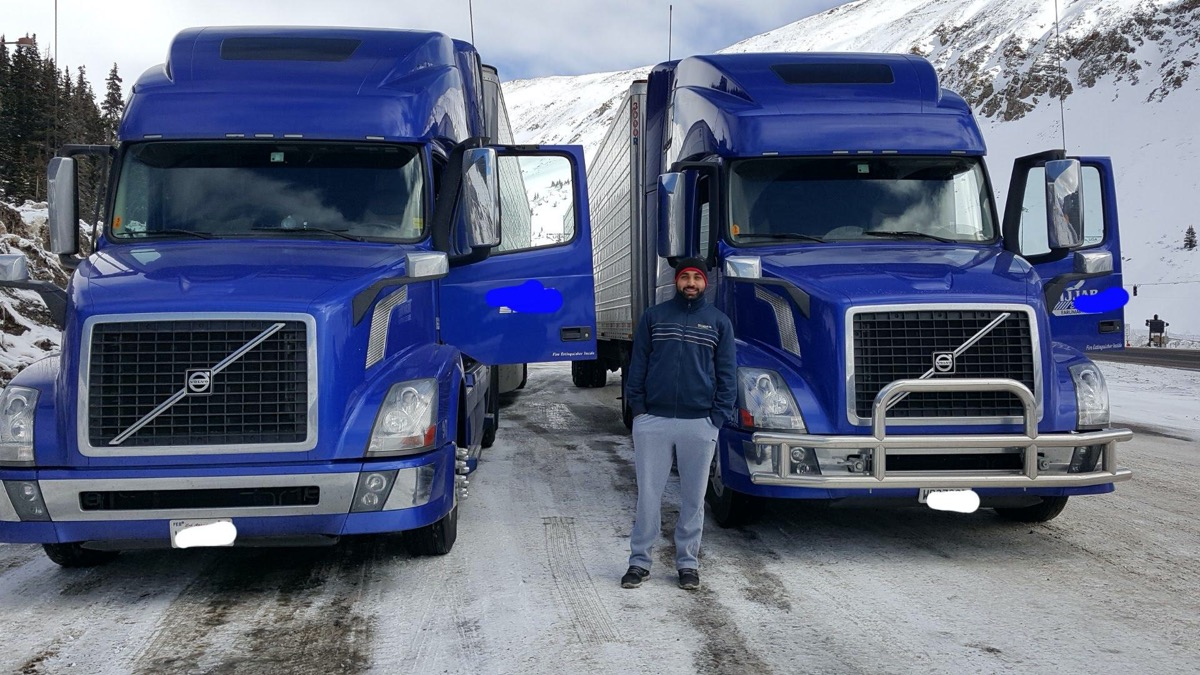 a man wearing a beanie, jacket, and sweats standing between two large blue delivery trucks in a snowy mountainous road