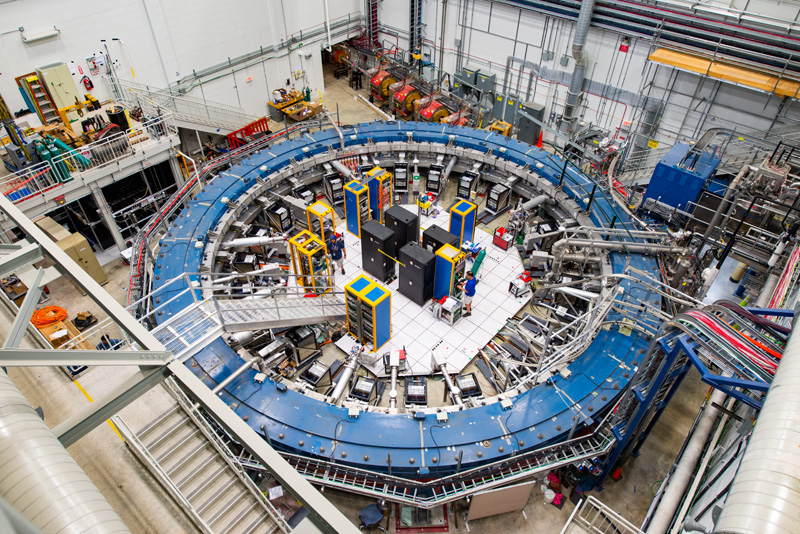 a look from above at a large blue circular lab equipment, the accelerator, in a warehouse-looking laboratory