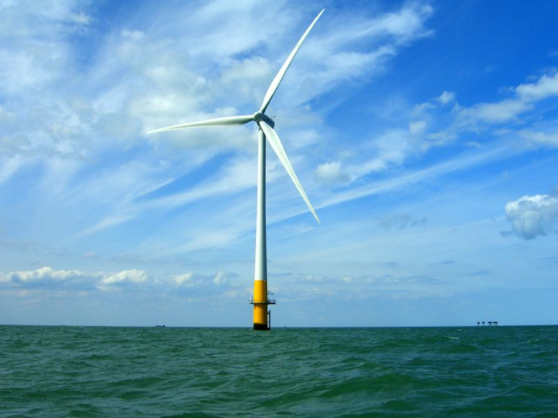a wind turbine in the ocean on a blue sky day